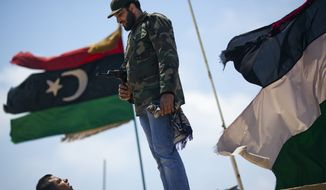 A rebel security officer stands guard Friday as people pray during Friday Prayer in Benghazi, Libya. (Associated Press)