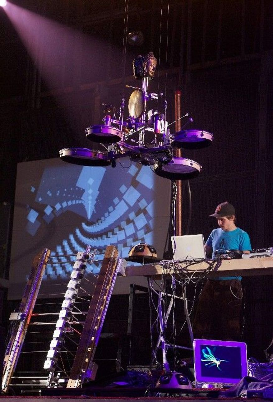 A California Institute of the Arts student tunes up a robot in preparation for a concert at the school's Walt Disney Modular Theater. The orchestra is composed equally of people and robots, with trained musicians manipulating and instructing the bots.