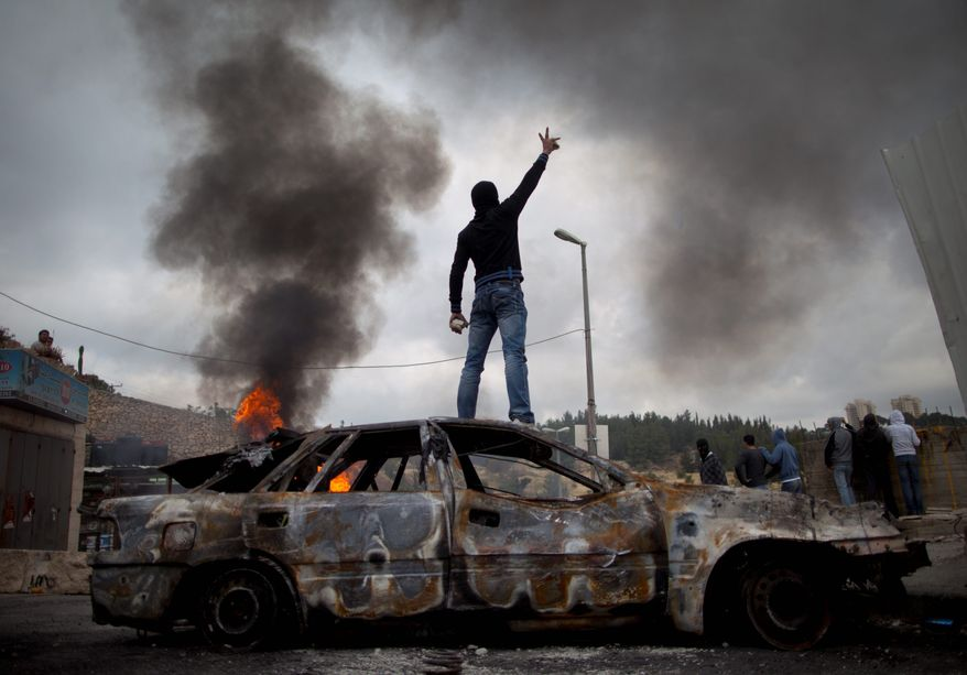 """ASSOCIATED PRESS HEATING UP: A Palestinian takes a stand during clashes with Israeli troops. Demonstrators were marking the 63rd anniversary of Israel's founding in 1948, what they call """"al-Naqbah,"""" or """"the Catastrophe."""""""