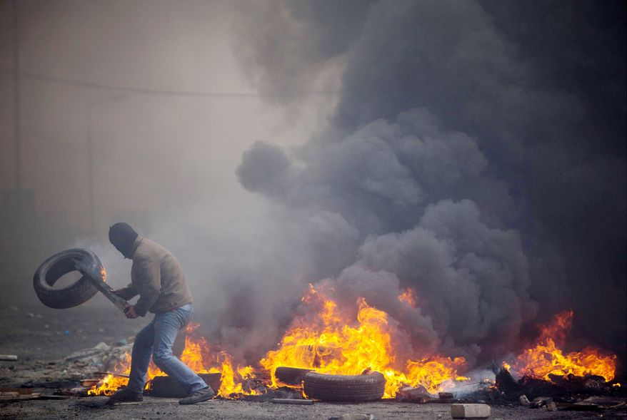 A Palestinian protester adds a tire to a burning barricade blocking the road during clashes with Israeli troops in the Shuafat refugee camp, on the outskirts of Jerusalem. At least 15 protesters were killed and many were wounded. Thirteen Israeli troops were injured.