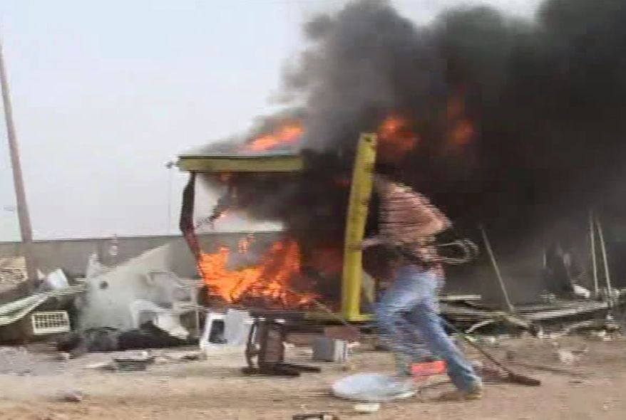 In this image taken from Associated Press Television News footage, an unidentified man runs away from a shelled checkpoint near the port area of Misrata, Libya, on Sunday, May 15, 2011 after Libyan government forces fired more than two dozen Grad rockets and mortars towards the area.  (AP Photo/APTN, Dalton Bennett)