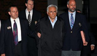Dominique Strauss-Kahn (second from right), managing director of the International Monetary Fund, is led from a New York police station where he was being held on Sunday, May 15, 2011, on charges of sexually assaulting a hotel maid. (AP Photo/Craig Ruttle)