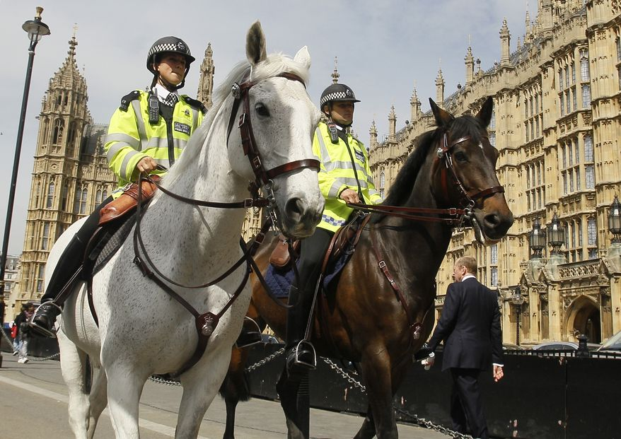 Mounted police patrol near Parliament in London on Monday, May 16, 2011, after British police received a bomb threat from a dissident Irish republican group ahead of Queen Elizabeth II's sensitive trip to Ireland on Tuesday.  (AP Photo/Kirsty Wigglesworth)