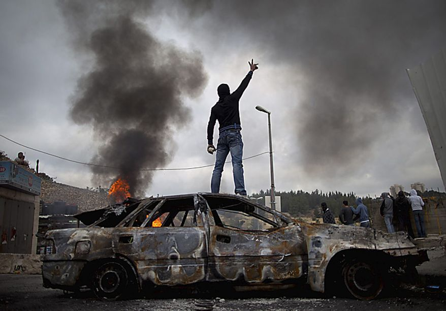 "A Palestinian demonstrator stands on a burnt-out car during clashes with Israeli troops, not seen, following a demonstration to mark the 63rd anniversary of ""Nakba"", Arabic for ""Catastrophe"", the term used to mark the events leading to Israel's founding in 1948, in the east Jerusalem neighborhood of(...)"
