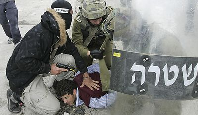 """A plainclothes Israeli police officer and soldiers detain a Palestinian protestor following a demonstration to mark the 63rd anniversary of """"Nakba"""", Arabic for """"Catastrophe"""", the term used to mark the events leading to Israel's founding in 1948, in the Qalandiya checkpoint between Ramallah and Jerus(...)"""