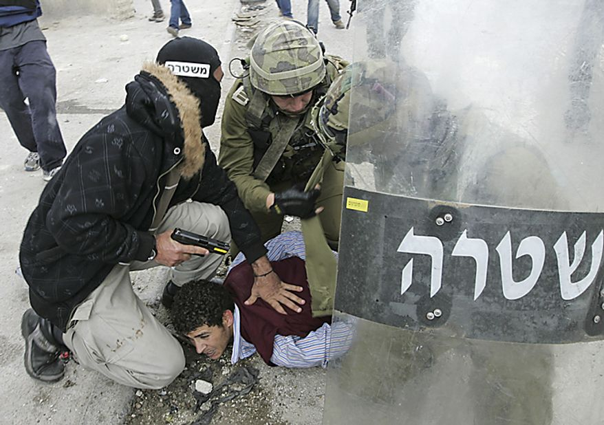 "A plainclothes Israeli police officer and soldiers detain a Palestinian protestor following a demonstration to mark the 63rd anniversary of ""Nakba"", Arabic for ""Catastrophe"", the term used to mark the events leading to Israel's founding in 1948, in the Qalandiya checkpoint between Ramallah and Jerus(...)"