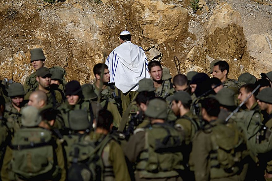 An Israeli soldier covered in a prayer shawl prays as Israeli troops gather near the border fence between Israel and Syria near the village of Majdal Shams in the Golan Heights, Monday, May 16, 2011. Mobilized by calls on Facebook, thousands of Arab protesters have marched on Israel's borders with S(...)
