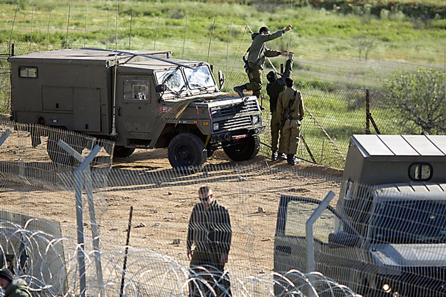 Israeli soldiers fix the border fence between Israel and Syria near the village of Majdal Shams in the Golan Heights, Monday, May 16, 2011. Mobilized by calls on Facebook, thousands of Arab protesters have marched on Israel's borders with Syria, Lebanon and Gaza on Sunday in an unprecedented wave of(...)