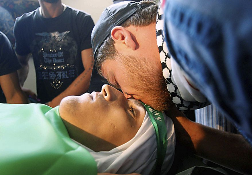 A Palestinian mourner, right, kisses the head of a Palestinian protester who killed when Israeli soldiers opened fire on Sunday at protesters who approached the northen Israeli border with Lebanon, during a funeral procession at Ein el-Hilweh Palestinian refugee camp, in the southern port city of Si(...)