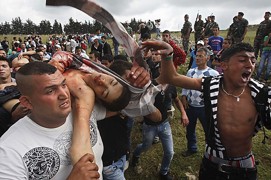 Protesters carry a Palestinian boy after he was injured when Israeli soldiers opened fire at protesters who approached the border with Israel during a rally in the southern border village of Maroun el-Rass, Lebanon, Sunday, May 15, 2011. Two Lebanese security officials say four people in Lebanon wer(...)