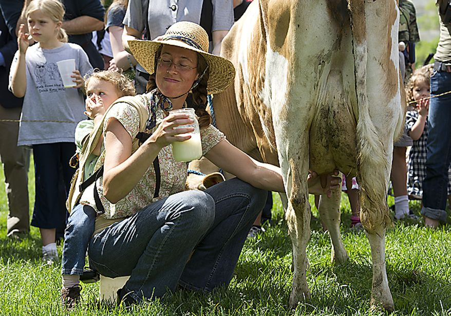 Leah Mack of Union Bridge, Md., holds a jar of milk she just got from Morgan the cow at a rally held by the organization Grassfed on the Hill at Upper Senate Park in Washington, D.C., on Monday, May 16, 2011. Fresh milk drinkers and advocates came out to protest the sting operation the FDA conducted against Pennsylvania dairy farmer Dann Allgyer and his private buying customers. (Barbara L. Salisbury/The Washington Times)