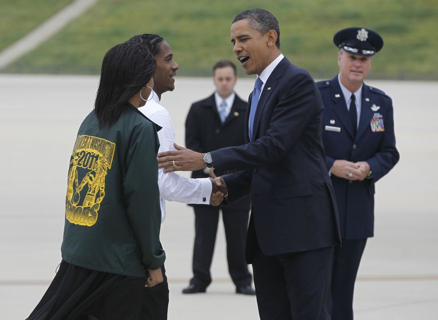 President Obama is greeted by Booker T. Washington High School students Cassandra Henderson (left) and Christopher Dean after stepping off Air Force One in Memphis, Tenn., for private meetings with families affected by flooding and to deliver the commencement address at Booker T. Washington High School. (Associated Press)