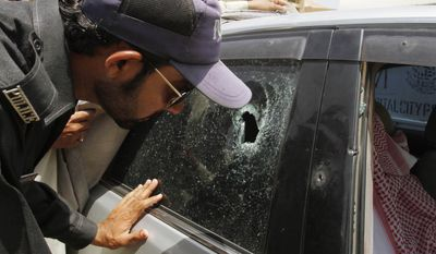 A Pakistani police officer examines a bullet hole on the car of a Saudi consulate employee who was shot dead in Karachi, Pakistan, on Monday. Gunmen on a motorbike shot and killed the Saudi diplomat as he was driving in Pakistan's largest city on Monday, police in Karachi said. (Associated Press)