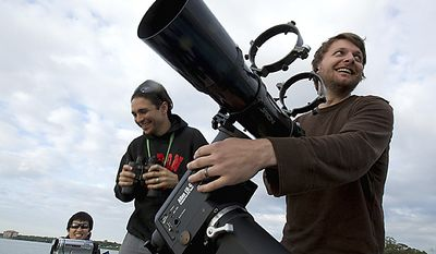 Brad Hill, right, and Jason Klav, from Nashville, Tenn., prepare their telescope to watch the space shuttle Endeavour launch at the Kennedy Space Center from Titusville, Fla., Monday, May 16, 2011. (AP Photo/Jason Greene)
