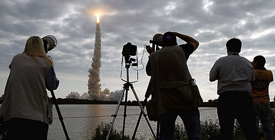 Photographers capture space shuttle Endeavour as it pierces the clouds and disappears after launch at Cape Canaveral, Fla., on Monday, May 16, 2011.  (AP Photo/J. David Ake)