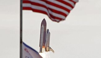 Space shuttle Endeavour flies past the US and mission flags after launch at Cape Canaveral, Fla., on Monday, May 16, 2011.  (AP Photo/John Raoux)