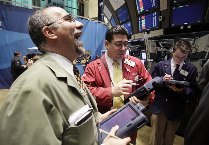 A trader laughs as he works May 12 with colleagues on the floor of the New York Stock Exchange. A loss of momentum on Wall Street, dropping commodity prices and worries over Europe's debt problems caused world stock markets to sag Monday. (Associated Press)