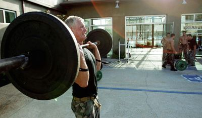 """ASSOCIATED PRESS Joe Stumpf, 54, lifts weights during a workout designed to mirror a Navy SEAL training regimen at the SEALFIT exercise center in Encinitas, Calif. """"If you really want to find out what's happening in Afghanistan ... you can come here and get a taste,"""" he said."""