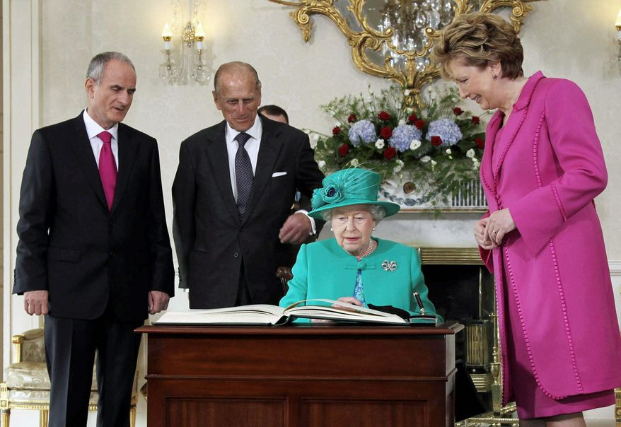 Queen Elizabeth II signs the visitor's book at Aras An Uachtarain, the Irish president's residence in Phoenix Park in Dublin on Tuesday. Irish President Mary McAleese; her husband, Dr. Martin McAleese (left); and Prince Philip look on. Politicians on both side of the Irish Sea have described the four-day event as momentous.