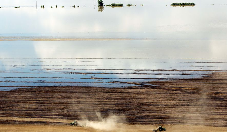 Farmers work as floodwaters from the Mississippi River creep across their fields Tuesday in Natchez, Miss. The Coast Guard said it closed the river at the port in Natchez because barge traffic could increase pressure on levees already burdened by heavy river flow. (Associated Press)