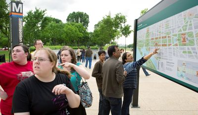 Friends (from left) Katie Devereaux, Laura Tucker and Kathryn Johnson discuss their next move at the detailed map of the Mall that made its debut Tuesday outside of the Smithsonian Metro Station. (Rod Lamkey Jr./The Washington Times)