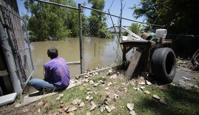 John Harrington sits Monday in the back yard of his friend's house as he watches the rising waters of the Atchafalaya River approach the property in Melville, La. (Associated Press)