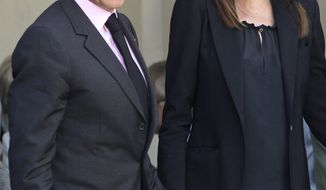 ** FILE ** French President Nicolas Sarkozy and his wife, Carla Bruni-Sarkozy, are seen on May 13, 2011, at the Elysee Palace in Paris. (Associated Press)
