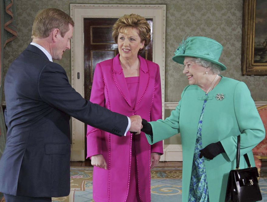 Britain's Queen Elizabeth II (right) is introduced to Enda Kenny (left), Ireland's taoiseach, or prime minister, by Irish President Mary McAleese at Aras An Uachtarain, the president's residence, in Phoenix Park in Dublin on Tuesday, May 17, 2011. The queen's visit is the first to the Republic of Ireland by a British monarch. (AP Photo/Tony Maxwell, Pool)