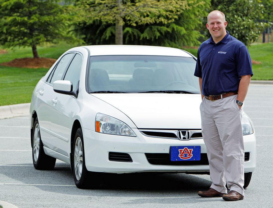 Jeremy Barnes shows off the 2007 Honda he is selling near his home in Greensboro, N.C. With used-car prices at 16-year highs, and a child on the way for him and his wife, Mr. Barnes is hoping to sell it for a good price. (Associated Press)