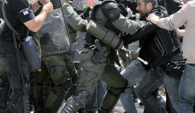 Protesters clash with police outside the Greek parliament during a demonstration by the Panhellenic Federation of Workers Association on Wednesday. The union is protesting the decision to increase working hours from 37.5 to 40 per week. (Associated Press)