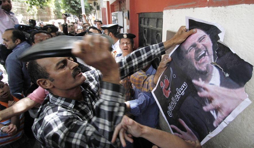 **FILE** A Syrian man beats a poster of Syrian President Bashar Assad with a shoe on April 26, 2011, during a protest in front of the Syrian embassy in Cairo, Egypt, against the ongoing violence in Syria. (Associated Press)