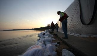 Personnel from the U.S. Army Corps of Engineers check sandbags along the shore of the rising Mississippi River in Natchez, Miss., on Wednesday, May 18, 2011. (AP Photo/Gerald Herbert)