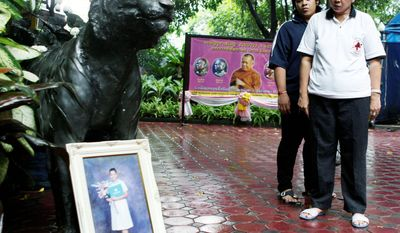 At Pathum Wanaram Temple in Bangkok last week, Payao Akkhahad and her son, Nattanakrit Akkhahad, look at a portrait of her daughter, Kamolkate, who was killed one year ago at the Buddhist temple. Kamolkate was a volunteer nurse when gunmen fired into the complex on the final day of militant anti-government demonstrations. (Associated Press)
