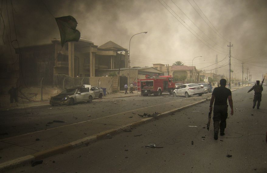 Security forces inspect the scene of twin bombings in Kirkuk, Iraq, 180 miles north of Baghdad, on Thursday, May 19, 2011. The blasts, which appeared timed to lure police out of their fortified headquarters, killed and wounded dozens of police officers. (AP Photo/Emad Matti)