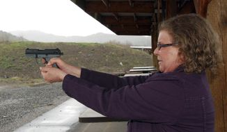 Cynthia Willis takes aim with her Walter P-22 pistol at a firing range in White City, Ore., on Friday, March 25, 2011. (AP Photo/Jeff Barnard, File) ** FILE **
