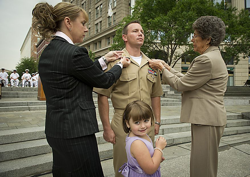 USN AWF1 (NAC/AW) James L. Henson (center) receives his pins from his wife Jeniece (left) and mother Robin Willson (right) while his daughter Avery Henson,4, (center) looks on during the Sailor of the Year 2010 ceremony at the U.S. Navy Memorial in Washington, D.C., Thursday, May 19, 2011. The Sailor of the Year program began in 1972 to recognize the outstanding Sailors of the Atlantic and Pacific Fleets. (Rod Lamkey Jr./The Washington Times)
