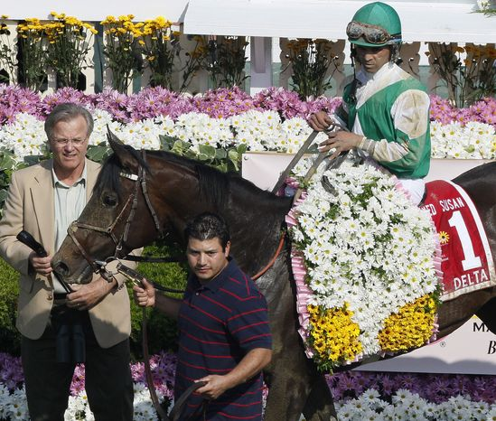 Royal Delta, with jockey Jose Lezcano aboard, is led to the winner's circle as trainer Bill Mott, left, looks on after winning the Black-Eyed Susan Stakes horse race at Pimlico Race Course, Friday, May 20, 2011, in Baltimore. (AP Photo/Patrick Semansky)