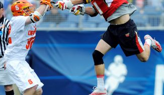ASSOCIATED PRESS Maryland's Kevin Cooper (right) takes a shot as Syracuse's Scott Loy defends during the first quarter in Foxborough, Mass. Grant Catalino scored in overtime to put the Terrapins in the NCAA semifinals.