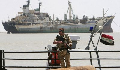 ** FILE ** A British soldier stands guard at the Umm Qasr port in Basra, Iraq, in May 2007. (AP Photo/Khalid Mohammed, File)