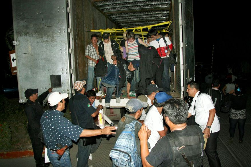 ** FILE ** Migrants from Latin America and Asia leave a truck that was heading to the United States after being detected by X-ray equipment at a checkpoint. Police in Mexico's southern Chiapas state found more than 500 migrants May 17 inside two trailer trucks. (Associated Press)