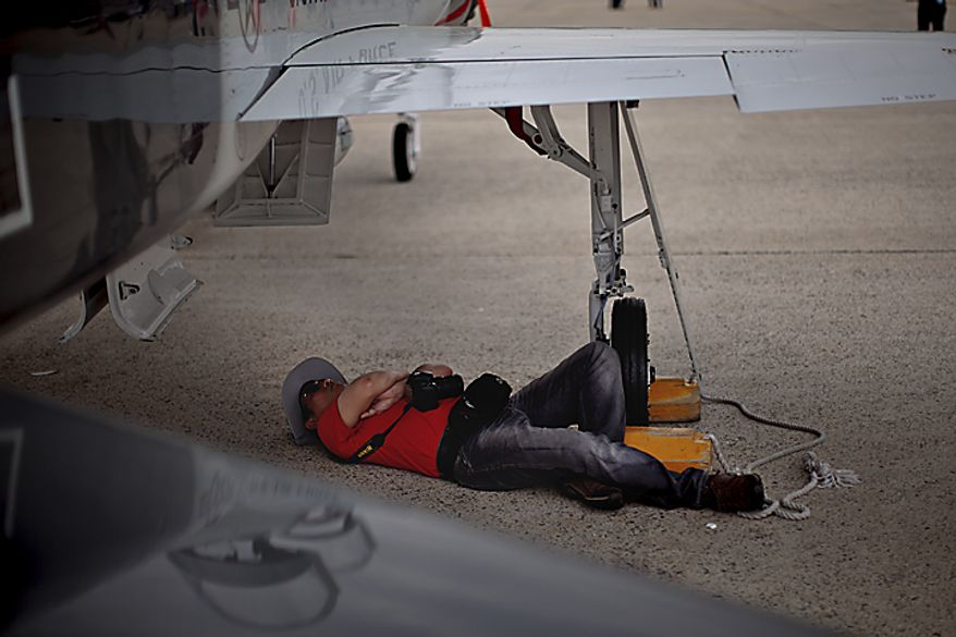A man takes a nap under the wing of a plane on display, during the Open House and Air Show at Andrews Air Force Base, Sunday, May 22, 2011. (Drew Angerer/The Washington Times)