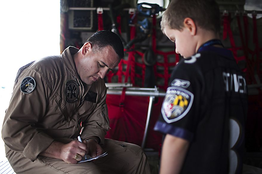 Gunnery Sargent Mike Gallardo, stationed in Newburgh, N.Y., signs an autograph for Jayden Armour, 6, of North Potomac, Md., inside of a Marine KC130 plane, during the Open House and Air Show at Andrews Air Force Base, Sunday, May 22, 2011. (Drew Angerer/The Washington Times)