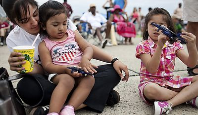 From left, mother Gabriela Gonzalez, of Silver Spring, sits with her daughters Leila, 2, and Valeria, 5, as they sit and play with toy Blue Angels airplanes, during the Open House and Air Show at Andrews Air Force Base, Sunday, May 22, 2011. It was the girls' first trip to the air show. (Drew Angerer/The Washington Times)