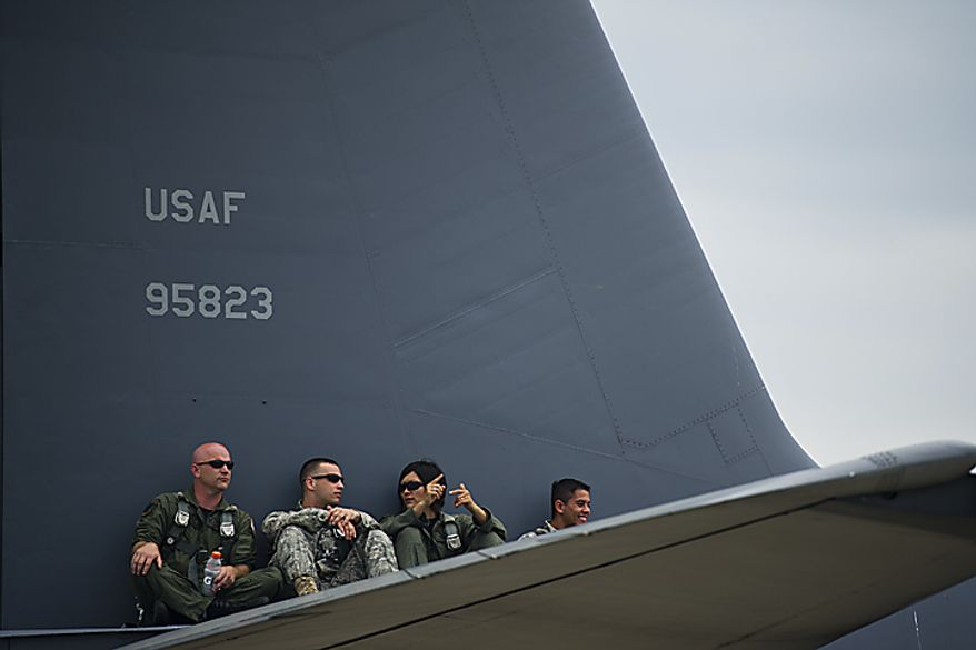 Crew members from the Marine KC-130 plane sit on top of the wing as they watch the U.S. Air Force Thunderbirds, during the Open House and Air Show at Andrews Air Force Base, Sunday, May 22, 2011. (Drew Angerer/The Washington Times)