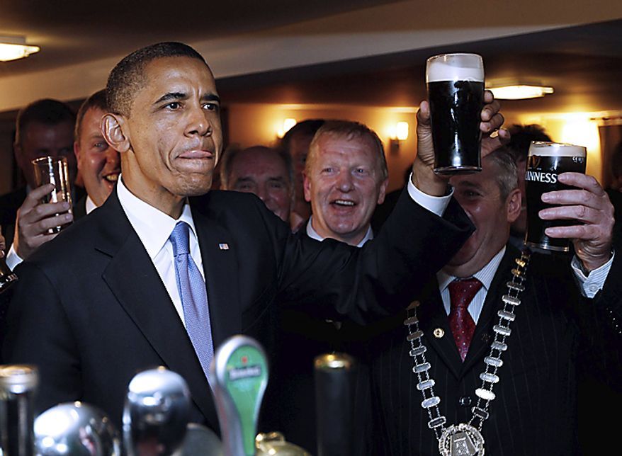 U.S. President Barack Obama drinks Guinness beer as he meets with local residents at Ollie Hayes pub in Moneygall, Ireland, the ancestral homeland of his great-great-great grandfather, Monday, May 23, 2011. (AP Photo/Charles Dharapak)