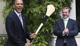 "U.S. President Barack Obama, left, reacts after he was presented with a hurley stick from Irish Prime Minister and Taoiseach Enda Kenny while in Farmleigh, Dublin Monday May 23, 2011. Obama said Monday that the U.S. and Ireland share a ""blood link"" that extends beyond strategic interests or foreign policy into the hearts of the millions of Irish Americans who still see a homeland here.(AP Photo, Pool)"