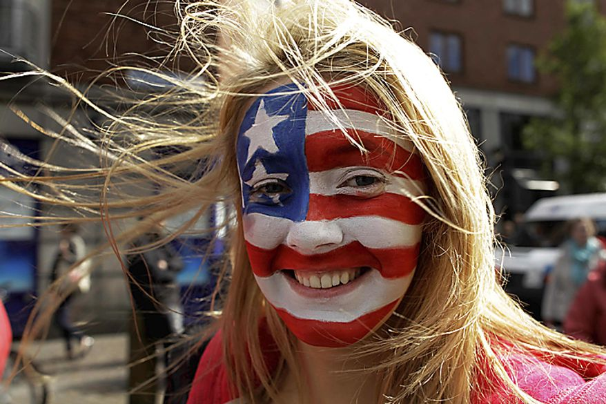 An Irish youngster poses for a photograph with a U.S. flag painted on her face amongst people queuing up to join the crowd to listen to U.S. President Barack Obama make an address at College Green in Dublin, Monday, May 23, 2011. President Barack Obama paid a joyful visit Monday to the small Irish village where his great-great-great grandfather once lived and worked as a shoemaker, an improbable and memorable pilgrimage for America's first black president into his Irish past. (AP Photo/Matt Dunham)