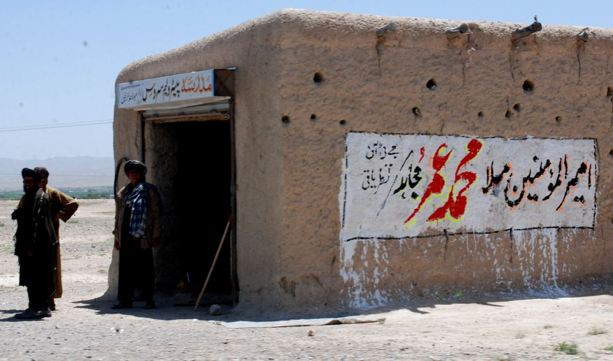 """** FILE ** Local residents stand outside a shop with graffiti reading """"leader of Muslims Mullah Mohammad Omar,"""" on Sunday, May 8, 2011, in Pashin, 100 kilometers south of Quetta, Pakistan. (AP Photo/Arshad Butt)"""