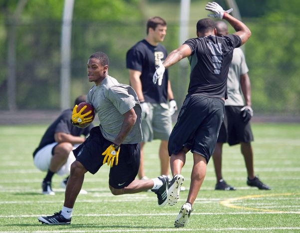 Washington Redskins rookie receiver Leonard Hankerson (left) pulls down a short pass as some members of the Washington Redskins hold an informal practice at a high school in northern Virginia, Tuesday, May 24, 2011. (Rod Lamkey Jr./The Washington Times)