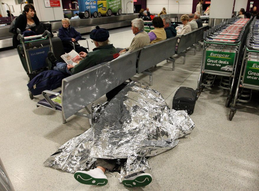 Passengers rest as their flights have been canceled at Edinburgh Airport in Edinburgh, Scotland, on May 24, 2011. A dense ash cloud from an Icelandic volcano blew toward Scotland, causing airlines to cancel flights and raising fears of a repeat of last year's huge travel disruptions in Europe that stranded millions of passengers. (Associated Press)